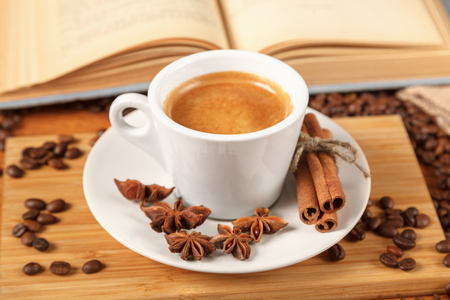 Coffee break a Cup of hot coffee and a book on a wooden table. A white Cup of black coffee surrounded by a small amount of roasted coffee beans, cinnamon, anise and an open book