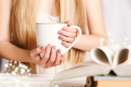 A Cup of tea in womens hands. Cozy concept for spring morning. Spring flower tea in a white Cup on the table with books and flowers. Reklamní fotografie