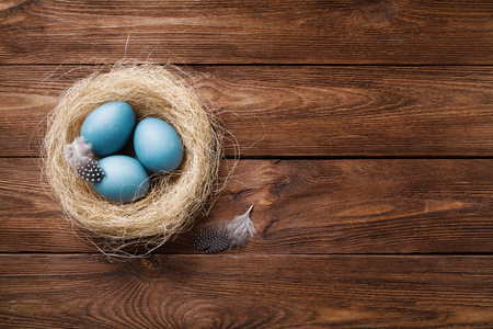 Three blue eggs in a nest on a wooden background, a symbol of spring, the religion of Christianity. Easter card. Three blue Easter eggs, painted with hibiscus, in a nest with feathers. Copy space 스톡 콘텐츠