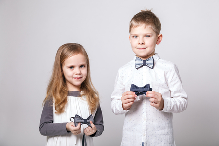 Cute boy and girl in fashionable clothes with bow tie posing on grey background. Portrait of fashionable children. The concept of children's fashion and style Imagens