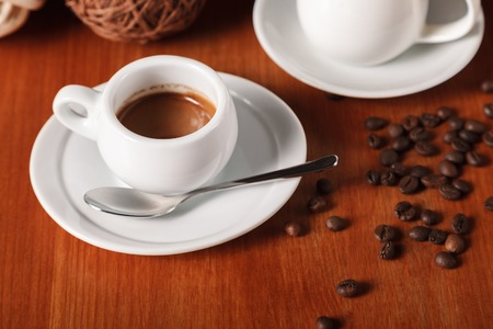 White espresso coffee Cup, roasted coffee beans and milk jug on wooden table background. The concept of coffee breaks and serving coffee