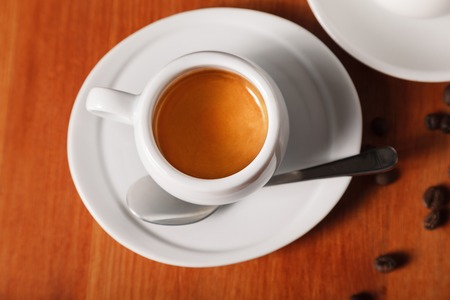 White espresso coffee Cup with delicious foam, close - up top view on wooden background. The concept of coffee breaks and serving coffee