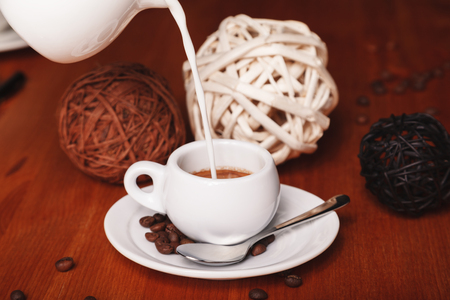 Pouring milk from the milkman into a small Cup of espresso coffee on a wooden background. The concept of coffee breaks and serving coffee 写真素材