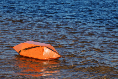 Safety on the water. A large orange buoy horizontally lies near the shore on the water of the Bay of the river 写真素材