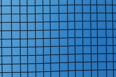 Iron fence on blue sky, mesh fence with blue sky, metal fence and blue sky background behind it.