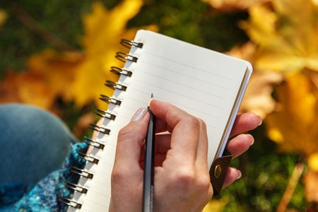 A woman's hand holding a paper notebook and pencil against the yellow leaves in the soft sunlight. Autumn mood, empty space for text