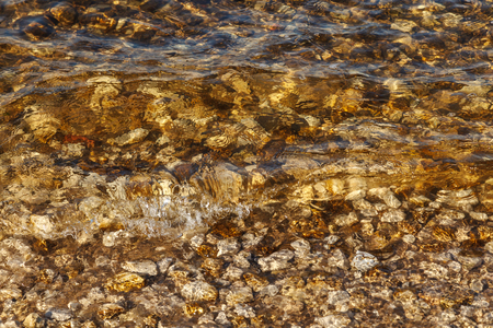 River waves near shore with rocky bottom. Transparent clean water waves. Abstract background texture of some smooth stones and sand in a river