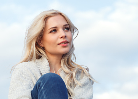 Beautiful happy blonde in a gray sweater and jeans smiling against the blue sky. Travel, leisure, tourism concept.