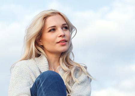 Hermosa rubia feliz con un suéter gris y jeans sonriendo contra el cielo azul. Viajes, ocio, concepto de turismo.