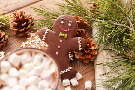 A beige Cup of traditional Christmas hot chocolate or cocoa with marshmallow. Traditional Christmas gingerbread, Christmas tree branches and cones on wooden background close-up, top view