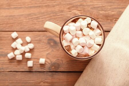 A Cup of traditional Christmas hot chocolate or cocoa with marshmallows on a wooden table, close-up, top view.