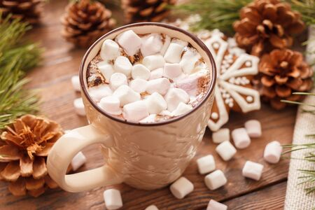 A beige Cup of traditional Christmas hot chocolate or cocoa with marshmallow. traditional Christmas gingerbread on wooden background close-up, top view 写真素材