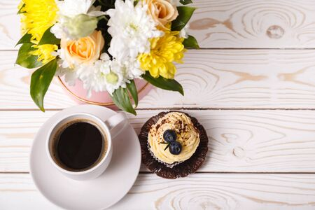 Cup of coffee, a cupcake with whipped cream and blueberries, a bouquet of spring flowers on a white background of a wooden table, top view. Romantic love background, mothers day greeting card