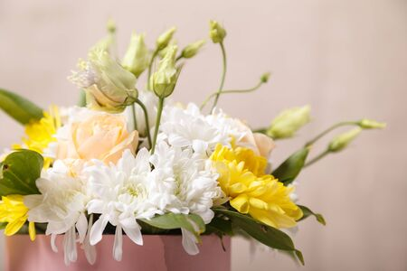 Flowers in a pink box close-up with a blurred beige background. Flowers as a gift, white chrysanthemums, yellow chrysanthemums, white roses, pink roses, as a background