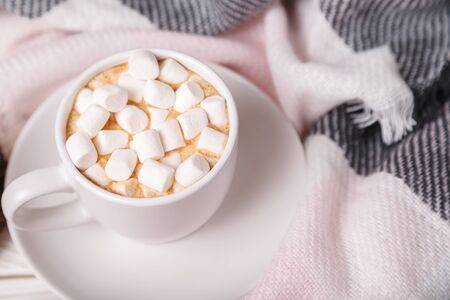 Hot cocoa in a cup with marshmallows on a bed with a white knit blanket. Festive cozy atmosphere. Cup of hot cocoa with marshmallows on background of wool plaid. Mock up. Flatlay
