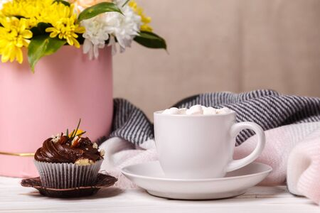 Cup of cocoa with marshmallows, a cupcake with whipped cream and blueberries, a bouquet of spring flowers and a soft blanket in the background. Valentines day, mothers Day, pleasant awakening