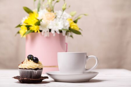 A white Cup of coffee and a cupcake with whipped cream and blueberries, a bouquet of spring flowers in the background. Romantic love background