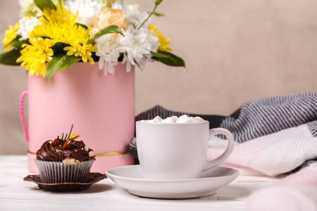 Cup of cocoa with marshmallows, a cupcake with whipped cream and blueberries, a bouquet of spring flowers and a soft blanket in the background. Valentine's day, mother's Day, pleasant awakening