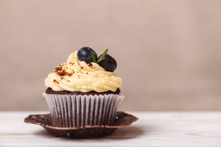 Delicious cupcake with whipped cream and chocolate on a blurred background of beige wall. Concept of advertising confectionery products