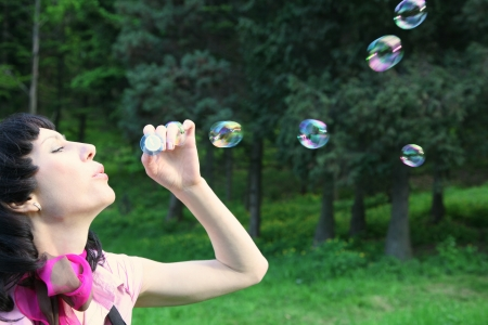 Happy carefree young brunette blowing soap bubbles photo