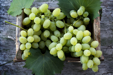Big clusters of ripe white grapes in a wooden box