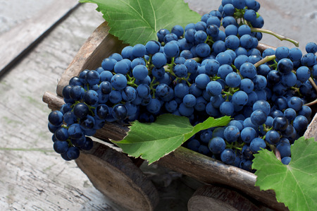 Big clusters of ripe blue grapes in a wooden box on a wooden background Banco de Imagens