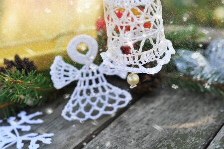 Christmas hand bell knitted hand on a festive background with the falling snow