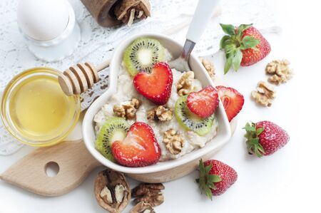 Breakfast with oatmeal with strawberries, kiwi, honey, walnuts and egg on white background. Breakfast for child. Oatmeal in a white heart-shaped plate. Top view