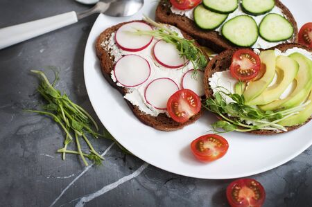 Vegetarian sandwiches with cream cheese, cucumber, avocado, garden radish, tomatoes and peas sprouts on white plate. Breakfast with vegetarian food.