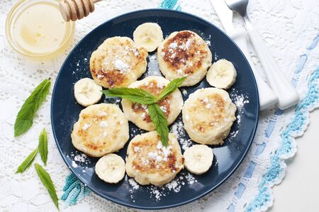 Cottage cheese pancakes, syrniki with banana and mint in blue plate. Top view