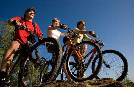 Three friends on bicycles on the brink of a rock and look afar from rock breakage  Stock Photo - 6353636