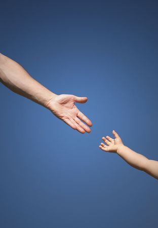 The children's hand reaches for a daddy's hand against the blue  sky Stock Photo - 6353620