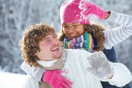 A young playful couple has a fun winter time in a snow park photo
