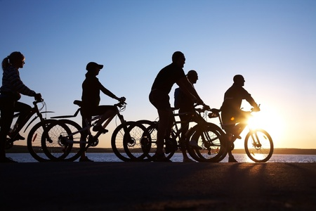 Image of sporty company friends on bicycles outdoors against sunset. Silhouette.  photo