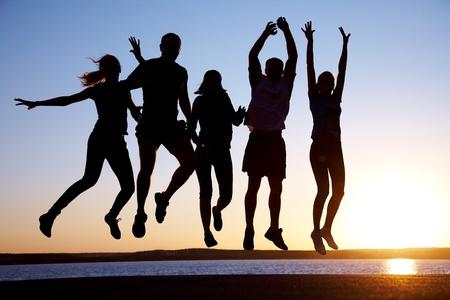 personas saltando: Grupo de j�venes felices, saltando en la playa en verano hermoso atardecer Foto de archivo