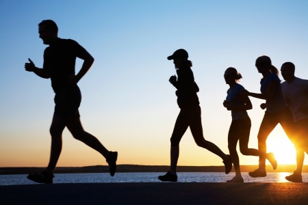 personas corriendo: Grupo de j�venes, que se ejecuta en la playa en verano hermoso atardecer Foto de archivo