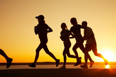 group of young people runs at the beach on beautiful summer sunset Stock Photo - 8370233