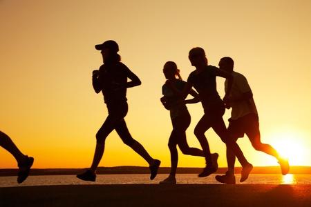 hacer footing: Grupo de j�venes, que se ejecuta en la playa en verano hermoso atardecer Foto de archivo