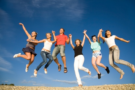 group of teens: group of happy young people dancing at the beach on  beautiful summer day