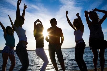chicas bailando: Grupo de j�venes felices bailando en la playa en verano hermosa puesta de sol
