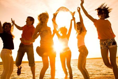 fiestas discoteca: Grupo de j�venes felices bailando en la playa en verano hermosa puesta de sol