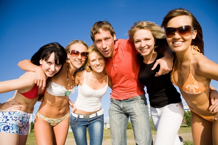 group of happy young people embrace at the beach on  beautiful summer day photo