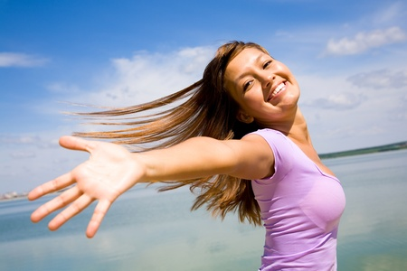 beautiful young woman opened her hands with delight at the blue sky Stock Photo - 8685558