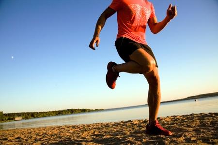 atleta corriendo: Joven corriendo a lo largo de la orilla del mar al atardecer.