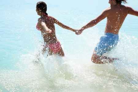 young couple in love runs into the sea holding hands photo