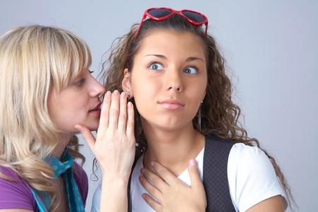 Girl tells a secret to her girlfriend photo