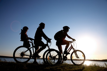 Young family go for a cycle ride on the beach at background sunset  photo