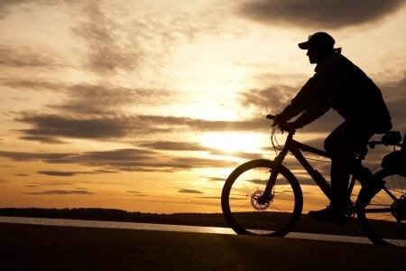 Silhouette der Radfahrer in Bewegung auf dem Hintergrund der sch�nen Sonnenuntergang