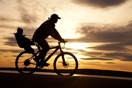 silhouette of cyclist with child in motion on the background of beautiful sunset photo