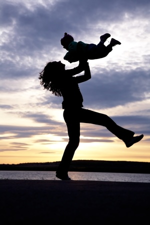 Silhouette of mother which turns the child against a sunset and water photo